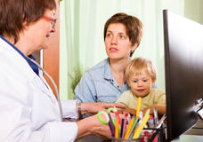 Woman with baby listening  pediatrician doctor Stock Images