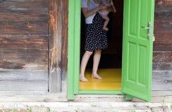 Woman with baby on open door Stock Photo