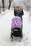 Woman with baby in perambulator walking in winter Royalty Free Stock Photography