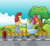 A woman and baby pram Stock Photos