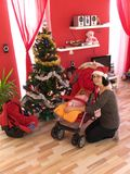 Woman and baby in red Christmas living room Royalty Free Stock Image
