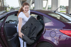 Woman with baby safety seat placing it in the car. Woman with baby safety seat placing it in the vehicle Royalty Free Stock Photography