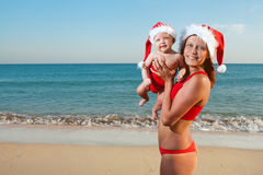 Woman and baby in santa hat on sea Stock Photo