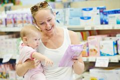 Woman with baby in shop Stock Image