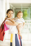 Woman with baby and shopping bags Royalty Free Stock Image