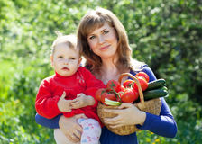 Woman and baby with vegetables in garden