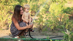 Woman with baby watered Royalty Free Stock Photos