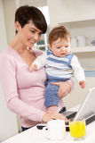 Woman With Baby Working From Home Stock Photos