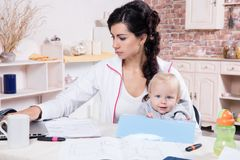 Woman With Baby Working From Home Stock Image