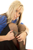 Woman back fishnets hold handcuffs look serious Stock Photo