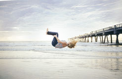 Woman Back Flip in Mid Air Beside Beach Under White Sky Stock Photos