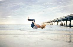 Woman Back Flip in Mid Air Beside Beach Under White Sky Stock Photography