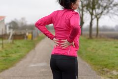 Woman with back or kidney pain clutching her back. Woman with back or kidney pain clutching her lower back as she takes a break from jogging or working out on a Royalty Free Stock Photography