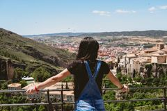 Woman from back looking at the city from a lookout stock photography