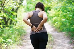 Woman with back pain, kidney inflammation, injury during workout. Outdoors concept stock photo