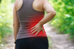 Woman with back pain, kidney inflammation, injury during workout. Outdoors concept stock images