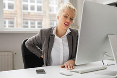 Woman with back pain sitting by the computer at the office Stock Photos