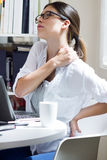 Woman with back pain at work Stock Photo