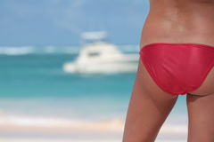 Woman back in red bikini on the tropical beach. Woman back in red bikini on the beach face to the  ocean with boat in background Royalty Free Stock Image