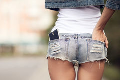 Woman back. Smartphone in jeans short pocket. Woman back closeup. Smartphone in jeans short pocket royalty free stock images