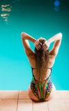 Woman back in swimsuit on pool edge. Stock Photos