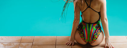 Woman back in swimsuit on pool edge. Royalty Free Stock Images
