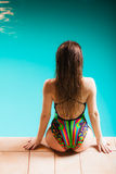 Woman back in swimsuit on pool edge. Royalty Free Stock Photography