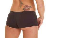 Woman back tattoo shorts. A woman has a tattoo of a rose and a humming bird on her lower back royalty free stock images