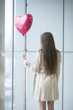 Woman with back to camera holding heart shaped balloon Stock Images