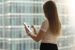 Woman back view swipe with finger on tablet screen. Standing woman back view swipe with finger on tablet screen. Businesswoman using modern touchscreen compact Stock Images