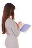 Woman from back, writing, holding notebook organizer in hand and Royalty Free Stock Photo