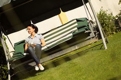 Woman in back yard on bench Stock Photography