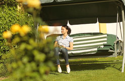 Woman in back yard on bench Royalty Free Stock Photography
