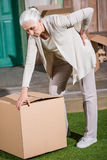Woman with backache standing on grass with big cardboard box Royalty Free Stock Photos