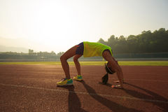 Woman backbending on stadium track Royalty Free Stock Photography