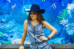 Woman in the background blue aquarium. Royalty Free Stock Images