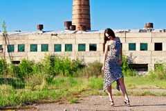 Woman on the background of the building. Fashionable woman stands against a background of an abandoned medical enterprise Royalty Free Stock Photo