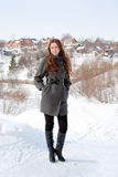 Woman on a background cottages in winter. Young woman on a background cottages in winter Royalty Free Stock Photos