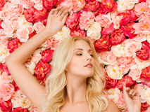 Woman and background full of roses stock photography