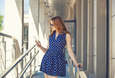 Woman on the background of a modern building with phone Royalty Free Stock Images