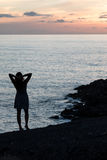 Woman on the background of the setting sun. Relax in the evening in the last rays of the sun Royalty Free Stock Photo