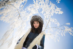 Woman on a background of snow-covered branches. Сute woman on a background of snow-covered branches Stock Photography