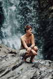Woman on the background of a waterfall Stock Image