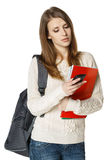 Woman with backpack and books sending a sms Stock Images