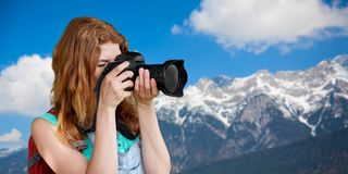 Woman with backpack and camera over alps mountains Stock Photography