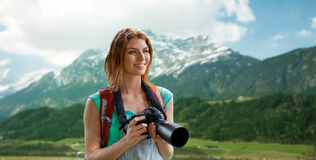 Woman with backpack and camera over mountains Royalty Free Stock Images
