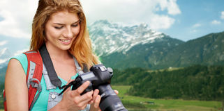 Woman with backpack and camera over mountains Stock Photo
