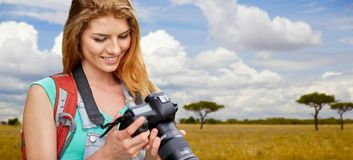 Woman with backpack and camera over savannah Stock Photo