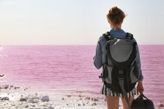 Woman with backpack on coast. Of pink lake royalty free stock photos