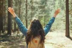 Woman with backpack and denim jacket stands with her back to the camera holding her hands up in the woods,selective focus. Brunette woman with backpack and denim stock photo